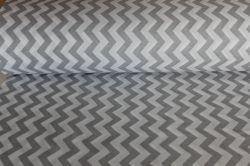 Bílá látka s tmavě šedým cik cak vzorem vyrobeno v EU